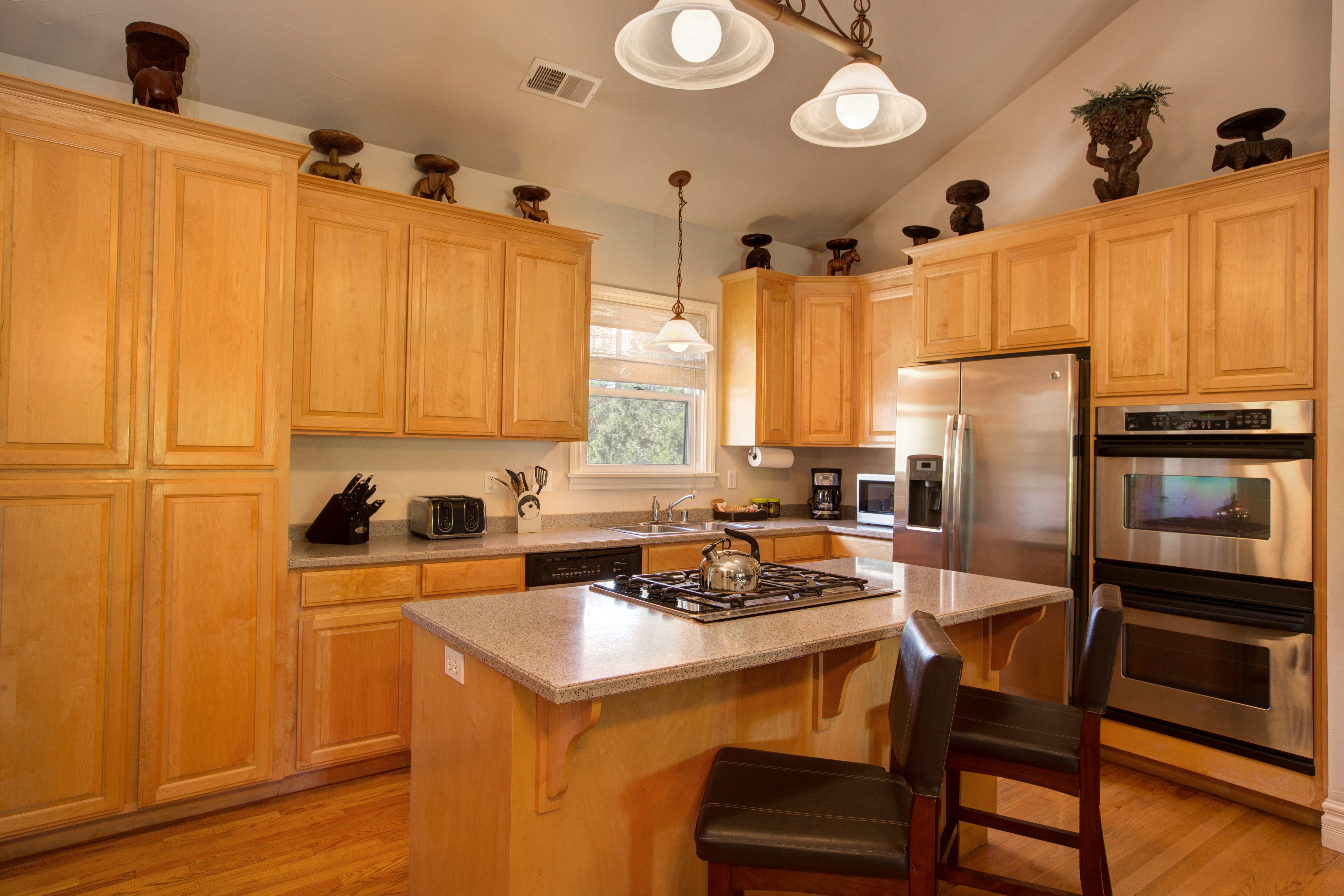 Vaulted kitchen with peach walls, shiny stone island countertop with smooth top electric stove, windows and doors with roman shades