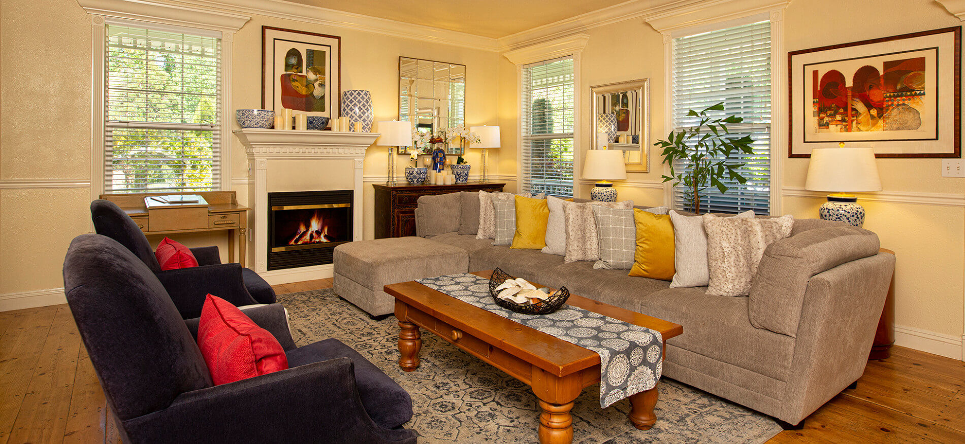 tan couch with ottoman in front of window, coffee table with runner,2 chairs, fireplace, lamps on stands