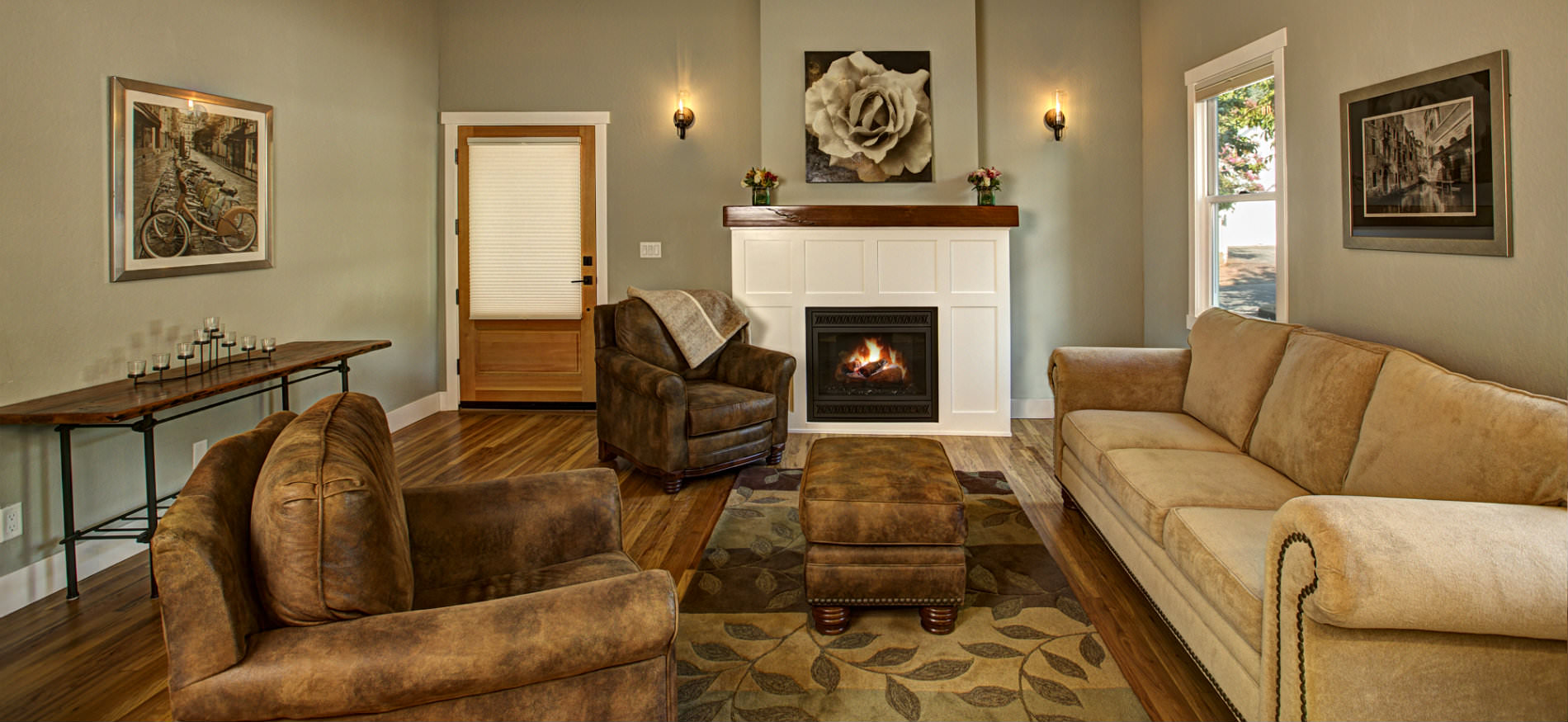 Sage green living room with wood floors a couch with two chairs and a warm fire in the fireplace