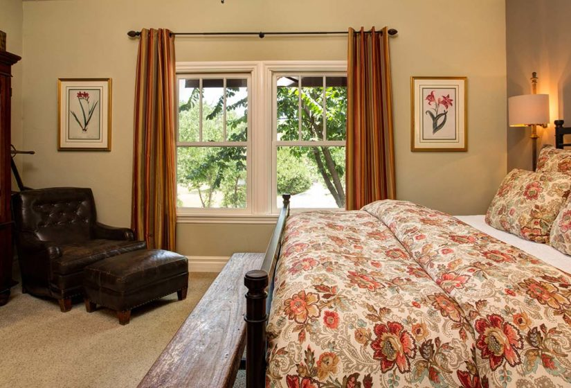 Interior view of bedroom with armoire, padded chair and expansive bed, looking out the tall curtain framed windows overlooking trees in the fore and background.