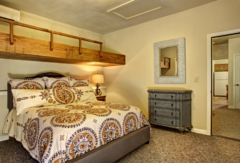 Bedroom with brown carpet, beige walls, large bed with ivory brown and blue comforter, a side bureau and mirror