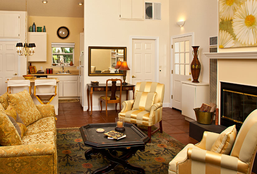 Open area with vaulted ceiling, gold furniture, fireplace, red tile flooring, and kitchen with white cabinets and yellow walls