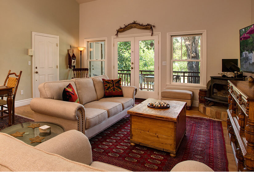 Vaulted bedroom with bed covered in red brown ivory and green floral comforter and a window with green trees outside